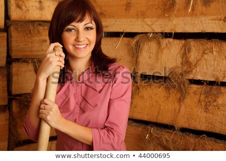 Portrait of girl in red shirt standing in hayloft against the wall of boards. Horizontal format. Stock photo © Paha_L