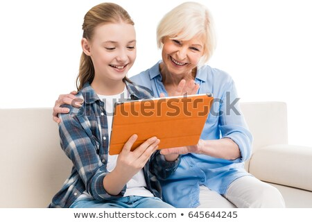 Smiling granddaughter and grandmother using digital tablet on sofa Stock photo © wavebreak_media