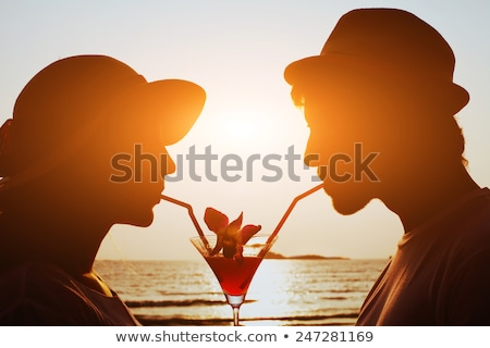 sunset tropical beach beautiful young woman silhouette drinking cocktail stock photo © orensila