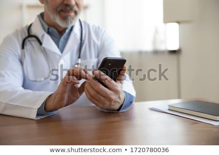 General practitioner using smartphone in office Stock photo © stevanovicigor