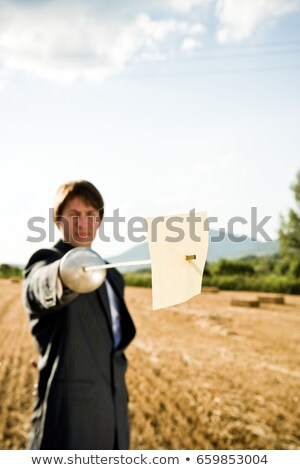 Businessman fencing in wheat field. stock photo © IS2