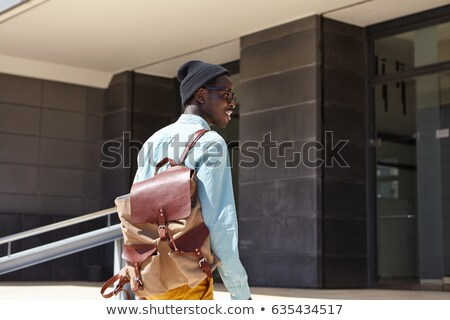 Happy casual man carrying backpack at the city street Stock photo © deandrobot