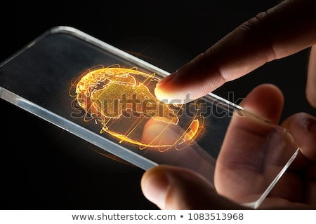 hand with smartphone and earth hologram Stock photo © dolgachov