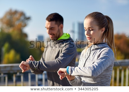 couple with fitness trackers running outdoors Stock photo © dolgachov