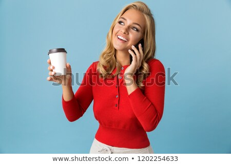 Stock photo: Portrait of joyous blond woman 20s holding takeaway coffee while