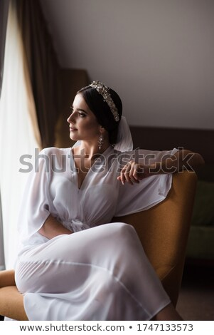 Bride in a wedding dress and veil looking at the window, waiting for the groom at the morning Stock photo © ruslanshramko