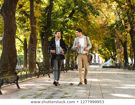 handsome young guy walking in park outdoors drinking coffee stock photo © deandrobot