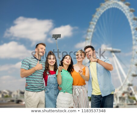 friends taking selfie over ferry wheel in london Stock photo © dolgachov