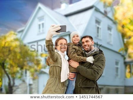 Stock photo: family takes autumn selfie by cellphone over house
