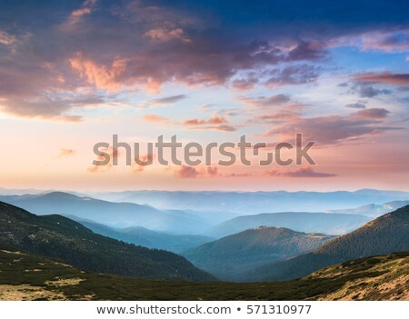 Sunset in the mountains. Dramatic colorful sky with blue hills Stock photo © galitskaya