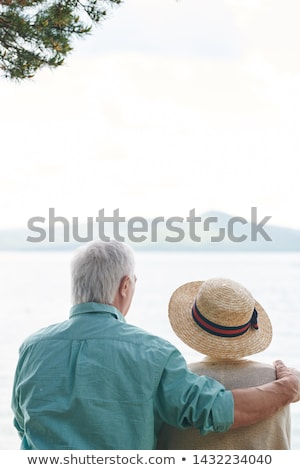Rear view of affectionate senior spouses sitting in front of lake Stock photo © pressmaster