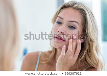 smiling woman applying cream to her cheek stock photo © kzenon