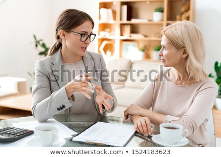 Stock photo: Young confident agent in formalwear answering questions of mature blond client