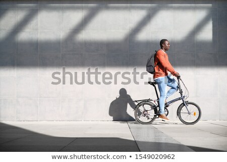 African Man Riding Folding Bike For Urban Commuting Stock photo © diego_cervo