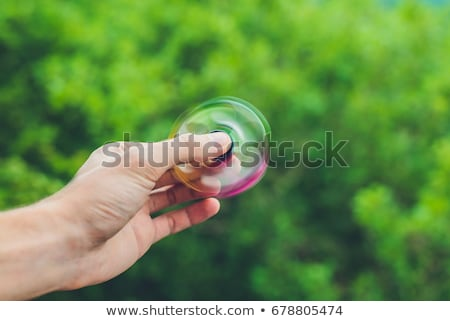close up of a mans hand who is holding a fidget spinner in a park stock photo © galitskaya