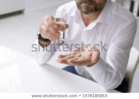 Elegant man in formalwear holding glass of water and painkiller over desk Stock photo © pressmaster