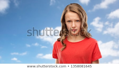 sad or angry teenage girl in red t-shirt over sky Stock photo © dolgachov