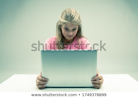 Young girl looking at her laptop with distaste Stock photo © Giulio_Fornasar