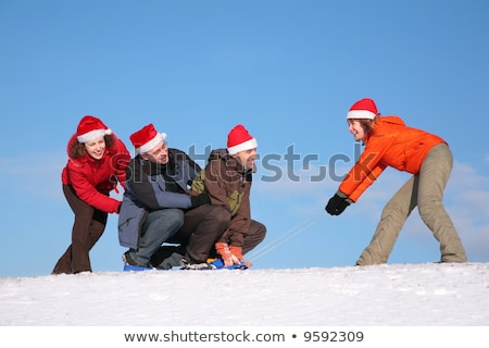 one woman pull two men on sled, other woman push them 2 Stock photo © Paha_L