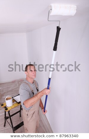 decorator using a roller extension to paint a ceiling white stock photo © photography33