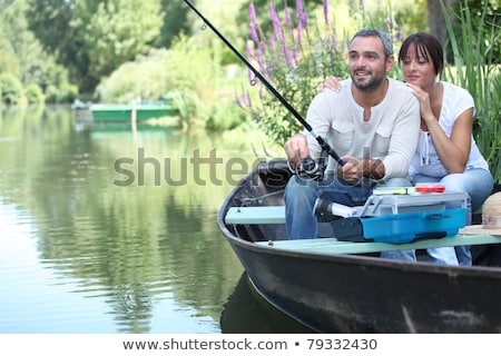 Stock photo: Couple fishing in a boat on a river