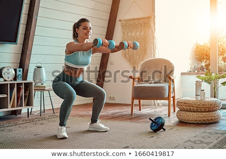 smiling fitness woman workout with dumbbells stock photo © deandrobot