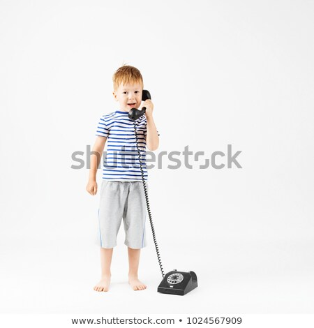 Portrait of boy in T-shirt talking to retro phone against white background. Isolation. Stock photo © Paha_L