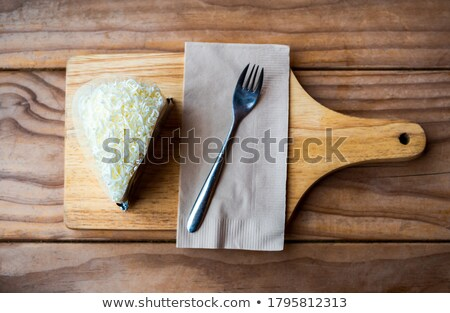 fresh tasty sweet piece of cheesecake on a white napkin and a dessert fork on a wooden background stock photo © mcherevan