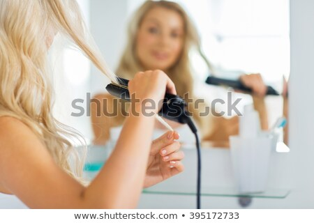 Cheerful attractive young woman straightening her hair with  straightener Stock photo © deandrobot