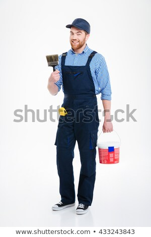 Happy bearded young man painter with can paint and brush Stock photo © deandrobot