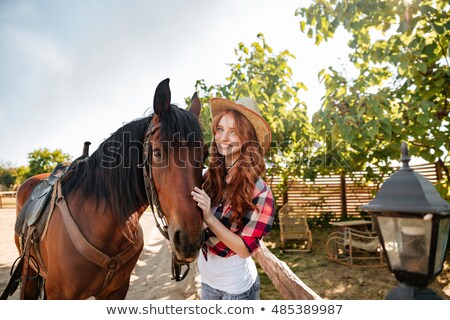 cheerful woman cowgirl sitting and riding horse in village stock photo © deandrobot