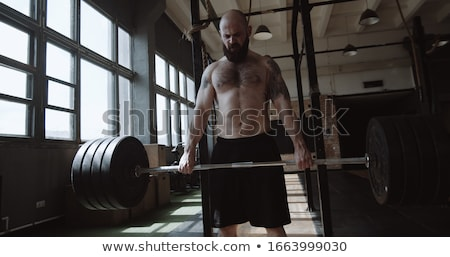 Workout with barbell in gym Stock photo © bezikus