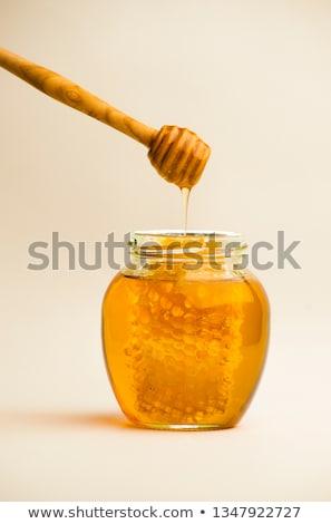 Honey in jar with honeycomb and wooden background. Stock photo © Yatsenko