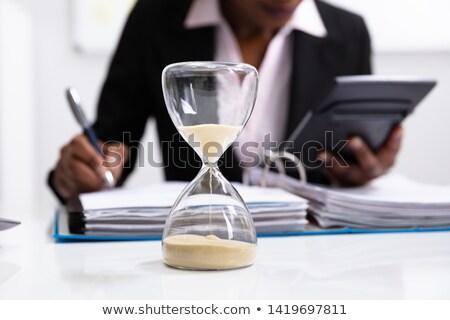 Businesswoman holding hourglass Stock photo © LightFieldStudios