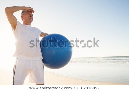 senior man holding exercise ball while standing at beach stock photo © wavebreak_media