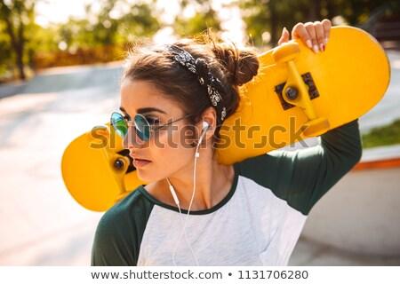 красивая женщина скейтборде улице глядя изображение Сток-фото © deandrobot