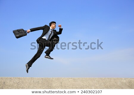 successful asian businessman jumping stock photo © rastudio