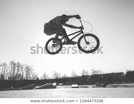 bmx biker jumping in city skate park outdoor   young trendy man stock photo © disobeyart