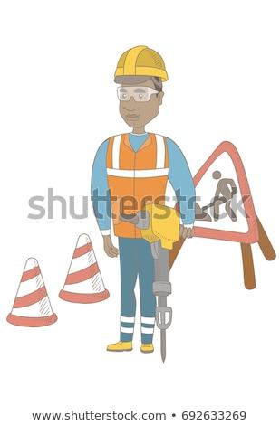 Young african builder using pneumatic hammer. Stock photo © RAStudio