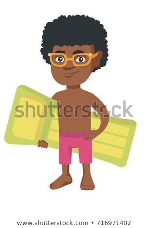 Little african boy holding inflatable mattress. Stock photo © RAStudio