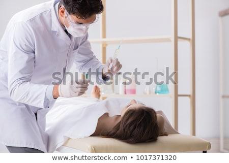 Police coroner examining dead body corpse in morgue Stock photo © Elnur
