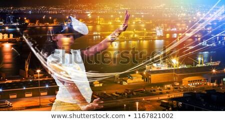 Girl gesturing while wearing virtual reality simulator against illuminated harbor against cityscape Stock photo © wavebreak_media