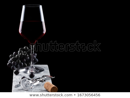 Glass of red wine on marble board with corkscrew opener and cork on black background. Space for text Stock photo © DenisMArt