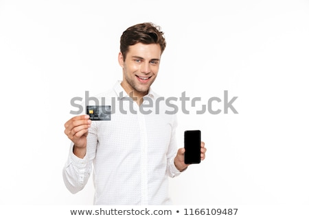 happy guy with dark hair holding mobile phone and credit card i stock photo © deandrobot