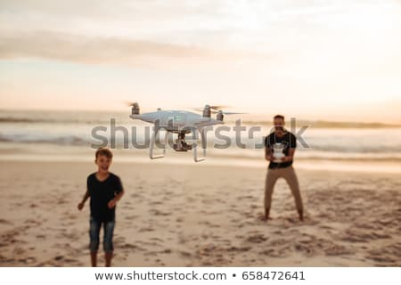 man operating a drone by a remote control outdoors stock photo © lightpoet