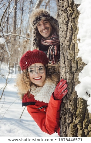 Playful couple hiding behind a tree trunk in the snow Stock photo © Kzenon