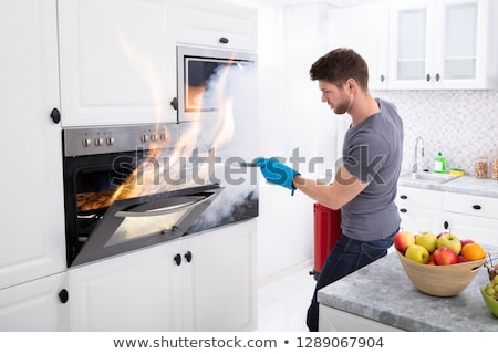 Man Trying To Stop Fire Coming Out From Oven Stock photo © AndreyPopov
