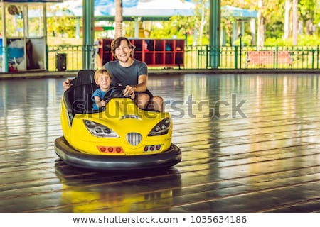 Father and son having a ride in the bumper car at the amusement park Stock photo © galitskaya