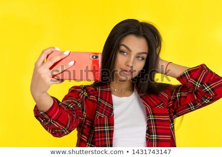 Stylish brunette woman making self portrait at yellow studio. stock photo © studiolucky