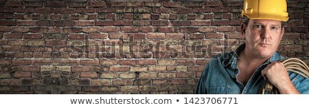 Male Contractor In Hard Hat Holding Cable In Front Of Old Brick  Stock photo © feverpitch